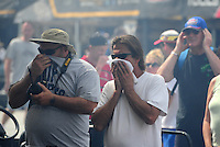 May 5, 2012; Commerce, GA, USA: NHRA fans in the pits cover their faces and ears as a car warms up during qualifying for the Southern Nationals at Atlanta Dragway. Mandatory Credit: Mark J. Rebilas-