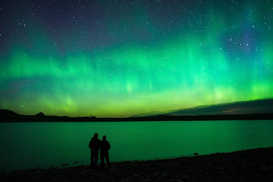 A couple takes in the view of the aurora borealis over Bean Lake near Augusta, Montana.