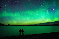 A couple takes in the view of the aurora borealis over Bean Lake near Augusta, Montana.