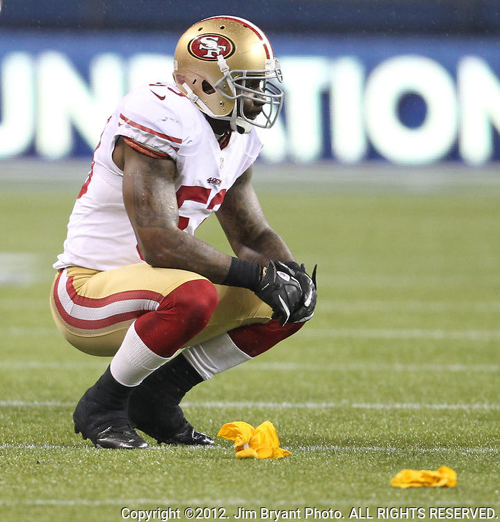 San Francisco 49ers linebacker Patrick Willis squats near yellow flags thrown after a play against the Seattle Seahawks at CenturyLink Field in Seattle, Washington on  December 23, 2012.     The Seahawks beat the 49ers 35-13. ©2012. Jim Bryant Photo. All Rights Reserved.
