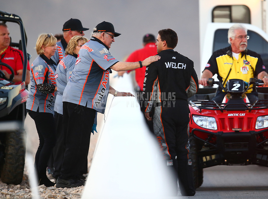 Oct 31, 2015; Las Vegas, NV, USA; NHRA funny car driver Brandon Welch with crew members after an engine fire during qualifying for the Toyota Nationals at The Strip at Las Vegas Motor Speedway. Mandatory Credit: Mark J. Rebilas-USA TODAY Sports