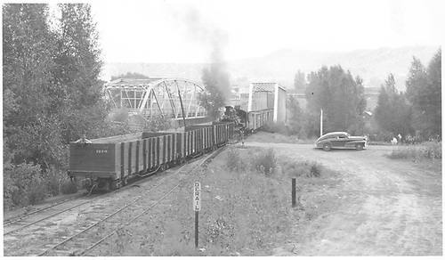 A wide-angle view as seen from the west side of the Las Animas River Bridge of a K-27 with a northbound freight.  Three gondolas are coupled to the pilot end in a switching move with a brakeman riding in the lead gon.<br /> RGS  West Durango, CO  Taken by Richardson, Robert W. - 8/7/1950
