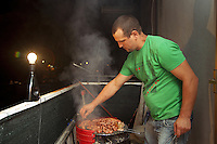 """Italy. Lazio region. Capena. Corneliu Siminiceanu is a romanian citizen and has lived in Italy for the last 10 years. He cooks mici on a open air barbecue on the flat's balcony. Mititei or mici , both Romanian words meaning """"small ones"""" is a traditional Romanian dish of grilled minced-meat rolls made from meat of beef, lamb and pork mixed, which contain garlic, black pepper, thyme, coriander, anise, savory and sometimes a touch of paprika. Sodium bicarbonate (and sometimes broth or water) is also added to the mixture. Romanian immigration. Capena (until 1933 called Leprignano) is a town and comune in the province of Rome. 24.09.2011 © 2011 Didier Ruef"""