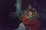 Eulalia Miguel and son Cristopher sleep as they ride a Greyhound bus at night through Texas on December 2, 2015. Miguel and her son fled Guatemala in 2015 because of domestic violence. After requesting political asylum in the United States, they were held for several days by immigration officials and then released, after which they stayed in a shelter run by the Refugee and Immigrant Center for Education and Legal Services (RAICES), and supported by a coalition of San Antonio churches. After that, they traveled by bus to a new location in the United States, where they will live pending a final decision on her request for asylum.