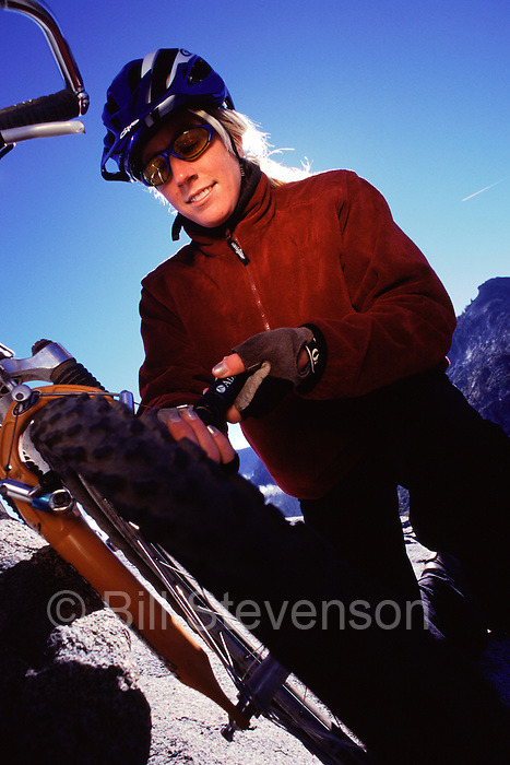 A picture of a woman inflating a mountain bike tire.