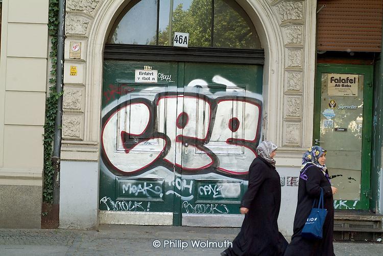 Muslim women in headscarves walk past graffiti in the largely Turkish Berlin neighbourhood of Kreuzberg