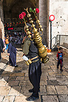 A Palestinian Arab man with his copper teapot on his back sells a cold drink made of tamarind juice and rose water by the Damascus Gate in East Jerusalem.  The Old City of Jerusalem and its Walls - UNESCO World Heritage Site