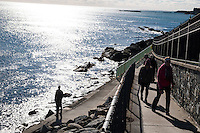 People walk along the Cliff Walk National Recreation Trail in Newport, Rhode Island, on Sat., Dec. 3, 2016.