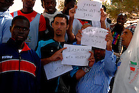 Lampedusa / Italia - 19 giugno 2011.Rifugiati all'interno della Base Loran, ex base NATO, dove vengono accolti i migranti minori non accompagnati. Nella foto mostrano cartelli di protesta durante la visita di Angelina Jolie e chiedono tempi più rapidi per documenti e trasferimento in altre sedi..Foto Livio Senigalliesi