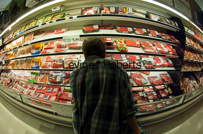 A shopper chooses a cut of meat in the butcher department in a supermarket in New York on Tuesday, September 18, 2012. (© Richard B. Levine)