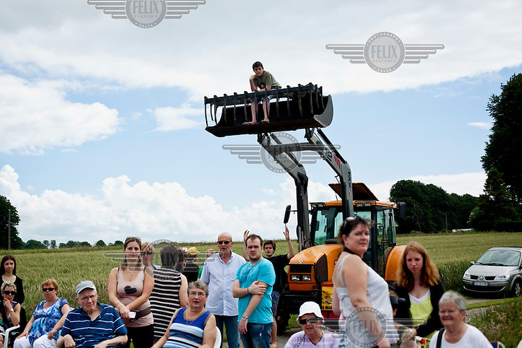 Locals wait on the side of a road including a child sitting in the lifting fork of a tractor as they wait see the Tour de France cycling competition pass through their village.