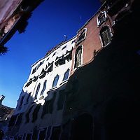 A building facade is reflected in the water of a canal in Venice, Italy in the summer of 2007.