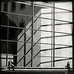 Two people sitting outside a modern glass building separated by a large obvious space