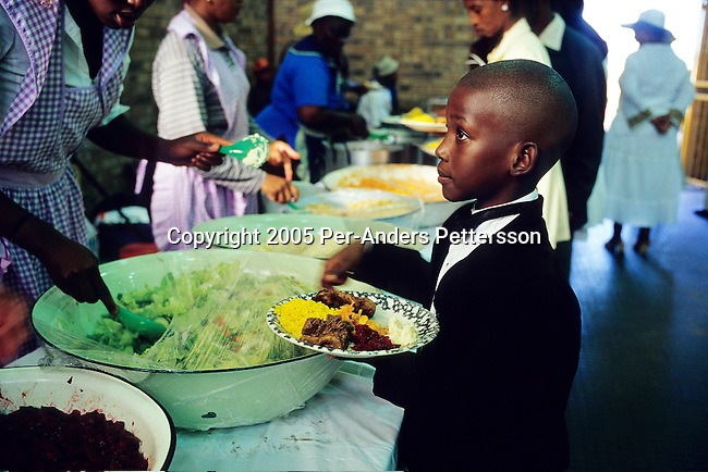SOWETO, SOUTH AFRICA MARCH 12: Kamogelo Jaleng, age 10,  receives food while attending a wedding reception on March 12, 2005 in Soweto, Johannesburg, South Africa. A couple celebrated a white wedding in a rented hall. Soweto is South Africa?s largest township and it was founded about one hundred years to make housing available for black people south west of downtown Johannesburg. The estimated population is between 2-3 million. Many key events during the Apartheid struggle unfolded here, and the most known is the student uprisings in June 1976, where thousands of students took to the streets to protest after being forced to study the Afrikaans language at school. Soweto today is a mix of old housing and newly constructed townhouses. A new hungry black middle-class is growing steadily. Many residents work in Johannesburg, but the last years many shopping malls have been built, and people are starting to spend their money in Soweto.  .(Photo by Per-Anders Pettersson/Getty Images).