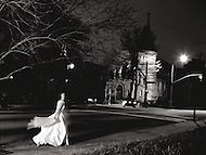 A woman walks at night towards a downtown church in her wedding dress
