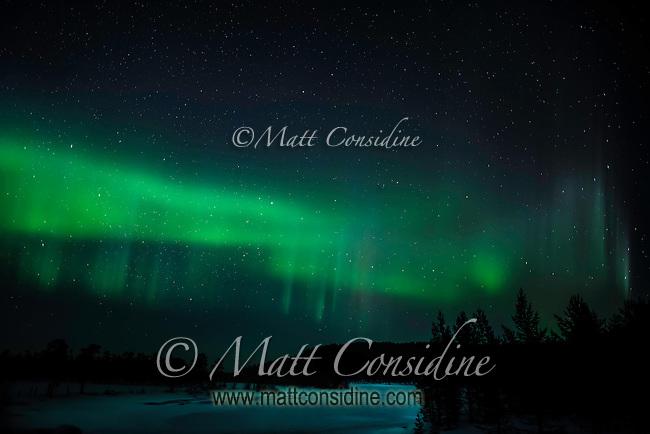 Strong green nortern light display over a frozen river. (Photo by Travel Photographer Matt Considine)