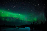 Strong green nortern light display over a frozen river. (Photo by Travel Photographer Matt Considine)
