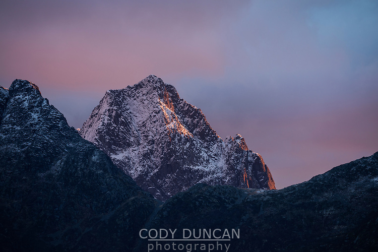 Mountain peak at sunrise with dusting of autumn snow, Austvågøy, Lofoten Islands, Norway