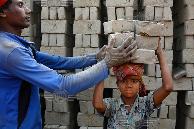 A man loads unfired bricks onto the head of a child working at a brick making factory in Gazipur. For each thousand bricks they move the labourers are paid the equivalent of about GBP 0.56.