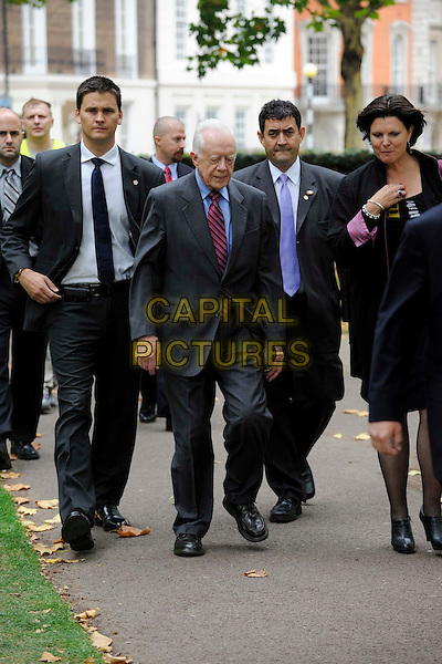 Jimmy Carter (James Earl Carter Jr.)  .Spotted walking in central London, England. .5th October 2011.full length black suit blue shirt red tie former president of the United States politics walking minders security guards .CAP/IA.©Ian Allis/Capital Pictures.