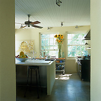 In the kitchen white-painted tongue-and-groove creates a rustic feel and an old-fashioned ceiling fan hangs above the kitchen island made of stucco and polished concrete