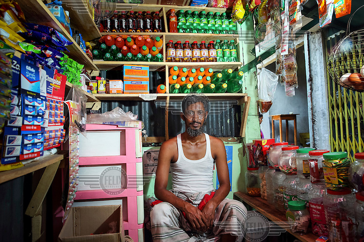 Khabir Uddin seated inside his wife's shop, the 'Siam General Store'.