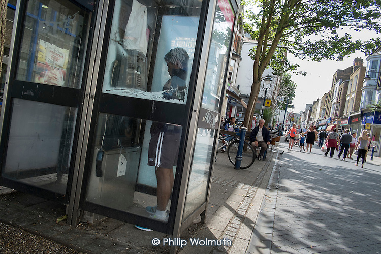 Boy in a vandalised telephone box in Ramsgate, one of the five most deprived seaside towns in the UK.