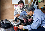 C.W. Nicol has tea and a chat with forest ranger Nobuyoshi Matsuki inside the ranger's hut in the C.W. Nicol Afan Woodland Trust, native woodland that Nicol began buying up 25 years ago, near his home in Kurohime, Nagano Prefecture, Japan on 10 May 2010..Photographer: Robert Gilhooly