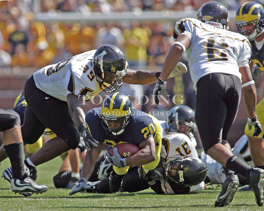 1 September 2007: Michigan running back Mike Hart is brought down rushing by Appalachian St defenders Colin McDonald (39) and Pierre Banks (31), in the 2007 season opener college football game between the Michigan Wolverines and Appalachian State Mountaineers at Michigan Stadium in Ann Arbor, MI. No. 5 ranked Michigan was upset 32-34.