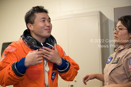 Houston, TX - (FILE) -- File photo dated December 22, 2008. Japan Aerospace Exploration Agency (JAXA) astronaut Koichi Wakata, dons a training version of his shuttle launch and entry suit in preparation for a training session in the Space Vehicle Mockup Facility at NASA's Johnson Space Center. Wakata is scheduled to join Expedition 18 as flight engineer after launching to the International Space Station with the STS-119 crew..Credit: James Blair - NASA via CNP