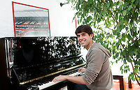 Il fuoriclasse del Milan Ricardo Kaka' ritratto al pianoforte al termine di un'intervista nel centro sportivo di Milanello, 17 marzo 2008. In alto a sinistra, un poster raffigurante la tifoseria del Milan..AC Milan star Ricardo Kaka' portrayed as he sits at the piano after releasing an interview at the club's sporting center in Milanello, near Milan, 17 march 2008. At top left, a poster of AC Milan fans is seen..UPDATE IMAGES PRESS/Riccardo De Luca