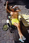 Artistic erotic portrait of a sexy young woman with shiny sweaty skin resting topless in a lounge chair drinking water from a bottle