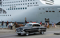 Havana, Cuba - A 1950s American car drives past a horse-drawn cart and a cruise ship on Avenida del Puerto near Havana harbor. Classic American cars from the 1950s, imported before the U.S. embargo, are commonly used as taxis in Havana.