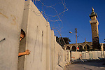 A Palestinian boy crosses the wall built to separate the Palestinian territories from Israel, June 10,2003, in the West Bank neighbourhood of Abu Dis, next to Jerusalem.