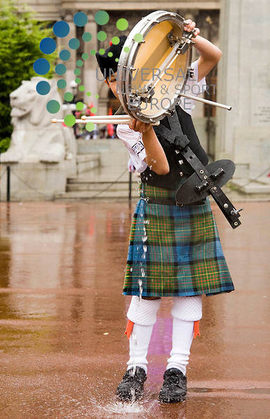 WET WET WET: Preview of World Pipe Band Championships, George Square Glasgow. Nine year old Logan Taylor from South Pasadena California U.S.A., tips the rain water from his drum.Picture/Johnny Mclauchlan/Universal News and Sport(Scotland)14/08/2009