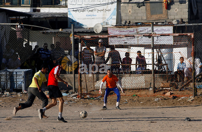 Palestinian youths play football before breaking fast in southern Gaza strip town of Rafah, on 03 August 2012. Muslims fasting in the month of Ramadan must abstain from food, drink and sex from dawn until sunset. Photo by Eyad Al Baba