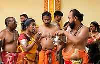 Nederland Den Helder  2016  06 26. Jaarlijkse tempelfeest bij de Hindoe tempel in Den Helder.. Vereniging Sri Varatharaja Selvavinayagar voltooide in 2003 het gebouw dat wordt gebruikt voor het bevorderen van kunst en cultuur. Een ander deel wordt gebruikt voor het praktiseren van religieuze waarden. Het hoogtepunt van de feestperiode is het voorttrekken van de wagen ( chithira theer of ratham ). Dit is een kleurrijke optocht, waarbij de godheid Ganesh in de wagen wordt voortgetrokken door gelovigen. Hindoepriester met kan. Rituelen in de tempel.  Foto Berlinda van Dam /  Hollandse Hoogte