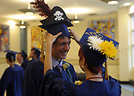 Mikey Martin of Hebron laughs as Delaina Pedri, of Marlborough, tries repeatedly to straighten his pirate cap, as RHAM students continue their long tradition of mortarboard decorating, prior to the RHAM High School graduation ceremony, Tuesday, June 18, 2013, at the school in Hebron.  (Jim Michaud / Journal Inquirer)