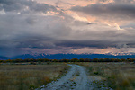 Idaho, Eastern, Driggs. Autumn colors  and colorful clouds at sunset above a country road in the Teton Valley.