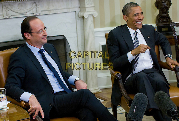 United States President Barack Obama meets with newly elected President Francois Hollande of France in the Oval Office of the White House in Washington, D.C. on Friday, May 18, 2012. The meeting comes at the start of a weekend that will include the G8 Summit held at Camp David in Maryland and the NATO Summit in Chicago, Illinois.  .half length blue suit sitting profile glasses smiling .CAP/ADM/KT.©Kristoffer Tripplaar/Pool/CNP/AdMEdia/Capital Pictures.