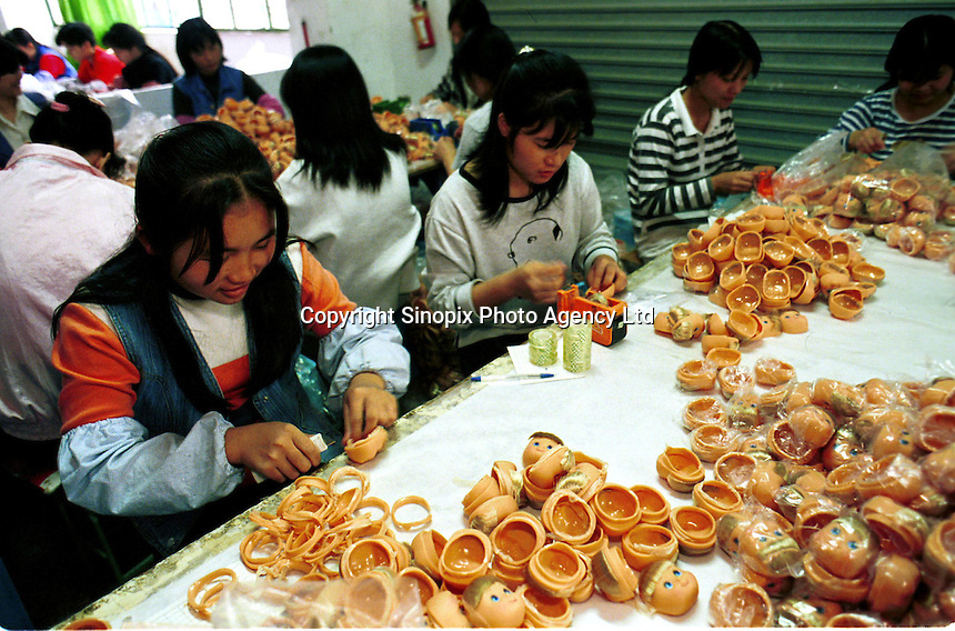 Female workers complete Christmas orders at a toy factory making dolls. Workers at this and other toy factories work and live in cramped conditions, earning for less than one pound sterling per day.
