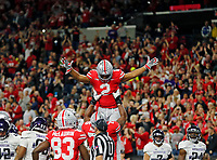 Ohio State Buckeyes offensive lineman Thayer Munford (75) throws up Ohio State Buckeyes running back J.K. Dobbins (2) into the air after he scored a touchdown against Northwestern Wildcats during the 1st quarter in the Big Ten Championship game in Indianapolis, Ind on December 1, 2018.  [Kyle Robertson/Dispatch]