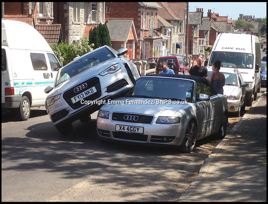 BNPS.co.uk (01202) 558833<br /> Picture: Emma Fernandez<br /> <br /> Vorsprung Durch Sandwich...<br /> <br /> Audi do that? -- A motorist accidentally lost control of their car and ended up parking on top of an almost identical motor. The motorist veered his silver Audi A6 into the back of a silver Audi A4 convertible as he leaned over to pick up a map that had fallen off the passenger seat. Luckily there was nobody inside the stationary Audi A4 at the time of the bizarre collision that happened in Swanage, Dorset.