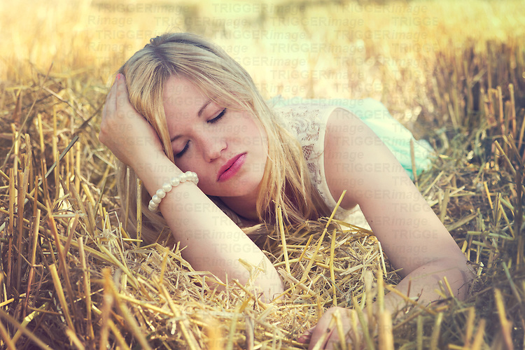 Young woman lying in the cornfield with eyes closed wearing a lace dress and pearl bracelet