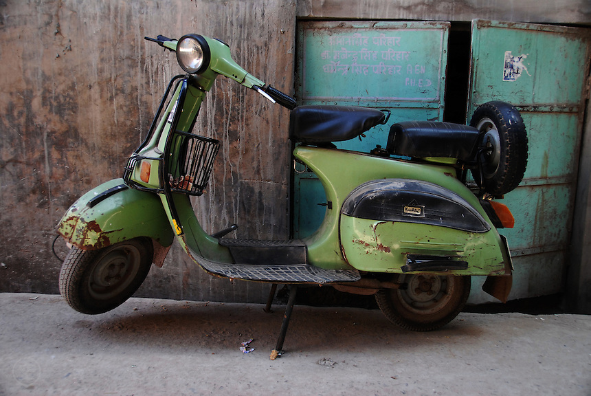 A green scooter parked against the blue detailed walls of Jodhpur, India