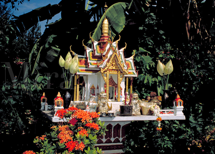 Buddhist spirit house in Northern Thailand. These houses are supposed to keep bad spirits away from the owners of the property. The door of the spirit house (and the Buddha inside) face outward. The Buddha statues are given offerings of flowers, ince nse,
