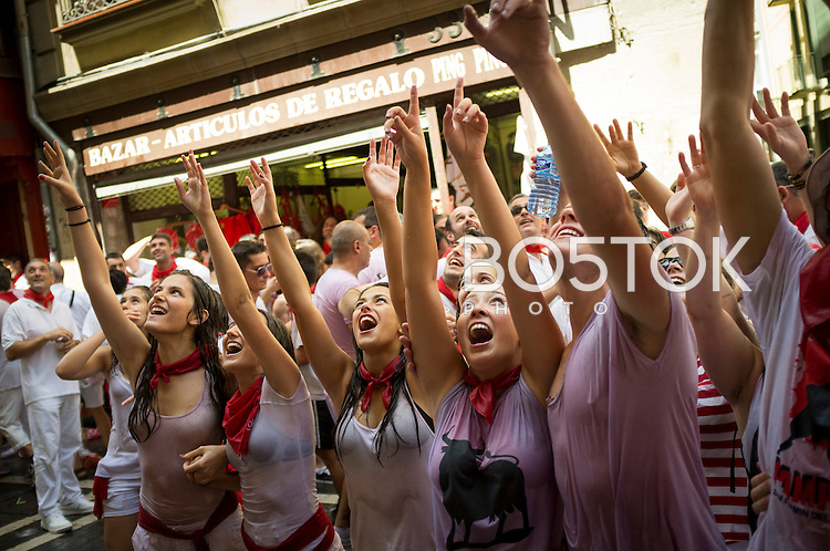 A group of people gets soaked with water thrown from the balconies while celebrating the opening of Sanfermin festival. Iruñea-Pamplona (Basque Country) July 6, 2015. Every year, tens of thousands of people pack Pamplona's streets for a drunken kick-off to one os world's best-known fiesta: the nine-day San Fermin bull-running festival. (Gari Garaialde / Bostok Photo)
