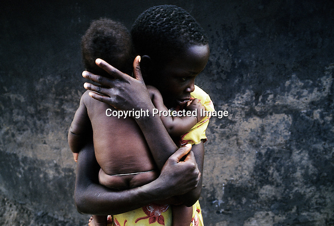 LALIYA, UGANDA - MAY 26: Susan Labol, age 10, hugs her little sister outside her family's hut on May 26, 2005 in Laliya, a rural village in Northern Uganda. Susan is a night commuter, one of about 20,000 children that sleep in Gulu town, as they are afraid of being abducted by the Lord's Resistance Army (LRA). The rebel group has brought terror to Northern Uganda for almost twenty years, fighting the Ugandan government. The victims are usually children, which are abducted and used as child soldiers and sex slaves. Susan walks 1.5 hours from her home village with her sister Gladys, age 12, every day to sleep at Noah's Arch, an NGO housing children in Gulu. They are too afraid to sleep in the village as an older sister was earlier abducted. She walks a further 30 minutes every day to attend school in a nearby village. (Photo: Per-Anders Pettersson)