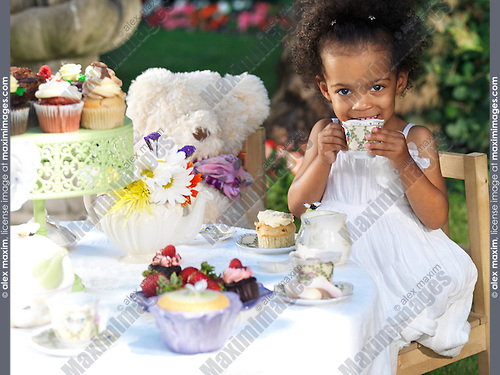 Happy smiling girl having an outdoor summer party. Drinking tea with cupcakes.