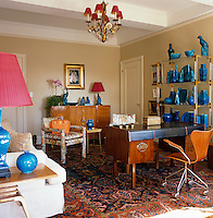 A striking collection of turquoise ceramic birds and vases is displayed on an etagere in the study